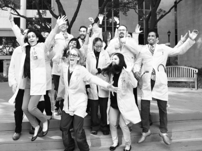 Image of Class of 2018 Pulmonary & Critical Care Medicine Fellows - Graduates Jumping in Celebration with White Coats at McGovern Medical School at UTHealth