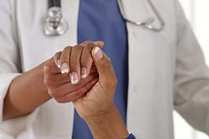 image of doctor holding hand of patient - diverse