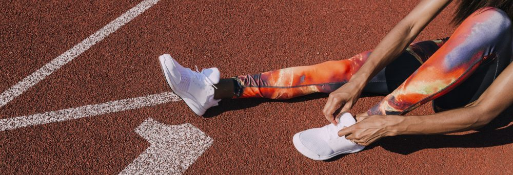 athlete on running tracks tying shoe