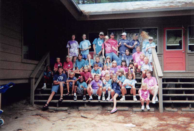 group photograph in front of cabin