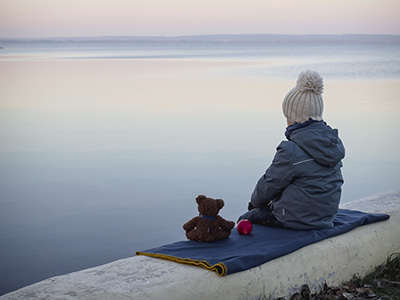 Child sitting on a winter pier at sunset with teddy bear