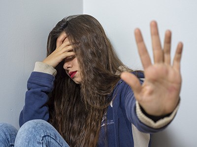 Sad young girl with depression sitting on the floor hand