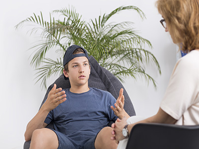 Problematic teenage boy talking with a woman psychologist, light interior