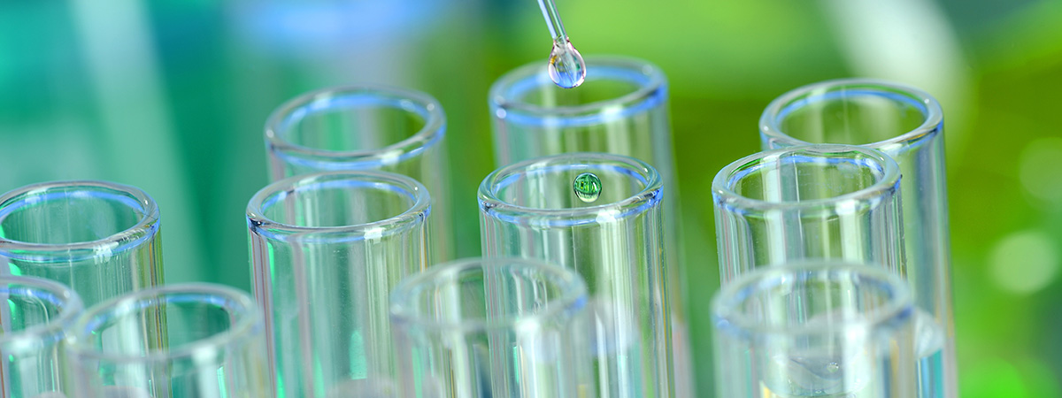 Laboratory glassware with pipette dropping fluid into test tube