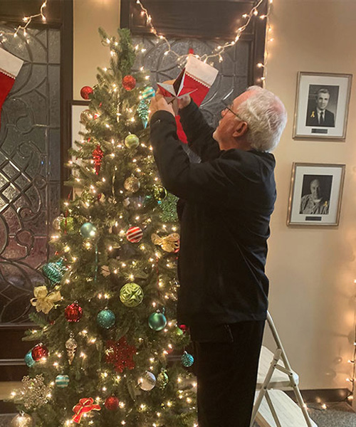 Dr. Andrassy putting the star on the top of the tree