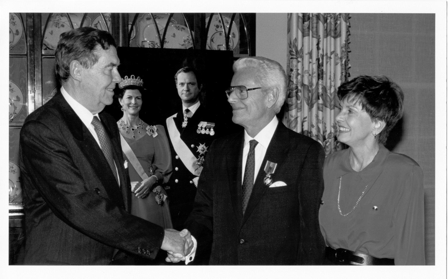 Dr. McGovern receiving the Royal Medallion of the Polar Star awarded in Houston by unidentified representative with the King and Queen of Sweden Award (pictured in the background)
